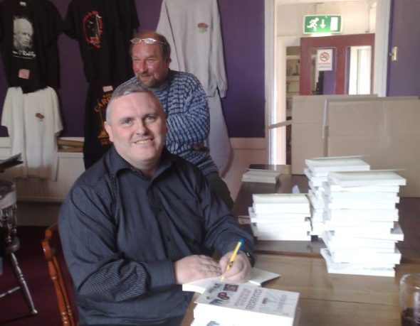 Signing copies of Shiprocked at the Radio Caroline sales stand. In the background is Mike Barrington, former engineer for both Caroline and Laser